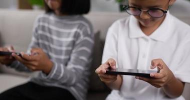 gros plan d'un garçon et d'une fille jouant au jeu sur téléphone. video
