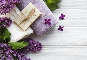 Spa towels and soap and lolac flowers photo