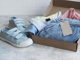 Clothes fir kids in an open cardboard box photo