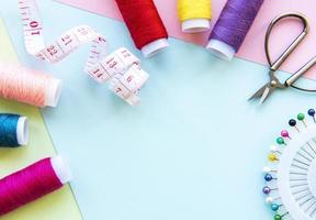 accesorios de costura sobre un fondo azul pastel foto