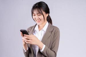 Joven empresaria asiática con teléfono sobre fondo blanco. foto