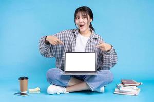 Estudiante asiática con expresión lúdica sobre fondo azul. foto