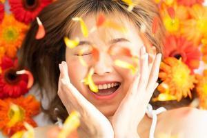 niña acostada sobre una flor con una expresión feliz foto