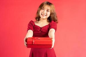 Joven asiática en vestido sosteniendo una caja de regalo roja con expresión alegre en el fondo foto