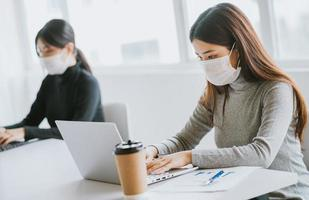 Two women have to wear masks during working hours to stay safe during epidemics photo