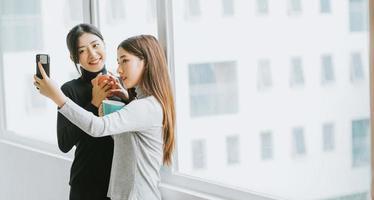 Dos mujeres de negocios asiáticas charlaban junto a la ventana durante el recreo. foto