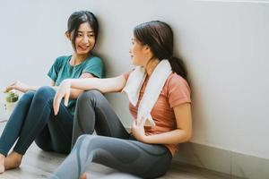 Two Asian women taking a break from yoga session photo