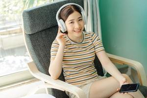 mujer acostada en una silla escuchando música relajante foto