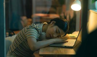 la mujer asiática se quedó dormida mientras intentaba terminar el trabajo por la noche foto
