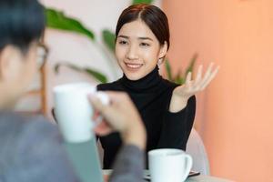 Mujer asiática sentada y charlando con colegas en la cafetería después del trabajo foto
