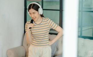 hermosa mujer asiática cantando en la sala de estar foto