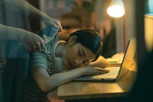 la mujer asiática se está quedando dormida mientras trabaja de noche, el marido está cubriendo a la esposa dormida foto