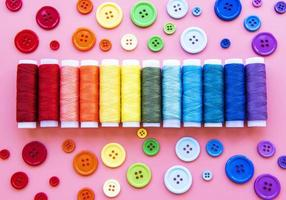 carretes de hilo y botones en los colores del arco iris foto