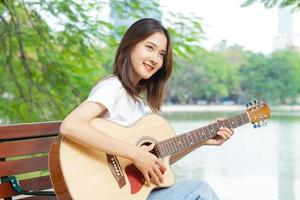 mujer asiática, tocar la guitarra, en la calle foto
