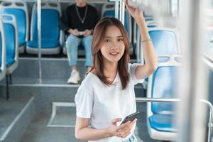 mujer asiática, utilizar, smartphone, en, autobús foto