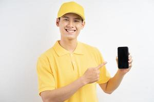 An Asian man in a yellow uniform was pointing at the cell phone in his hand photo