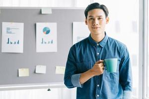 Asian man holding coffee cup standing smiling with planning board background photo