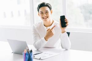 hombre de negocios asiático apuntaba al teléfono. empresario asiático está trabajando en su oficina foto