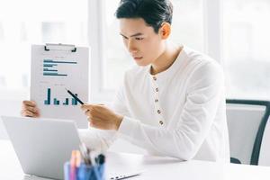 El empresario asiático participa en una reunión en línea con su equipo mediante una videollamada foto