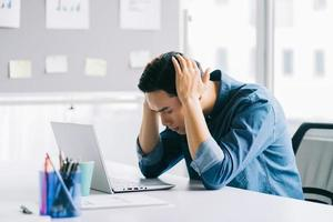 The Asian man is holding his head tired of having to work too much photo
