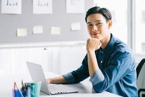 hombre de negocios asiático puso su mano en su barbilla y sonrió foto