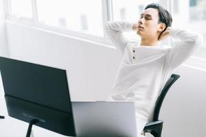 Asian programmer sits with his head back in his chair to relax after a tiring working time photo