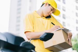 Asian shipper is calling the customer to get the goods photo