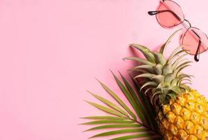concepto de verano con piña, gafas de sol y hojas de palmera sobre fondo rosa foto