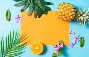 Fondo de verano con naranja, piña, flores y hojas sobre fondo azul. foto