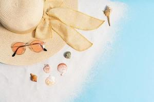 Summer background with hat, sunglasses, sand and seashell photo