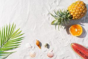 la playa de arena está decorada con frutas tropicales y hojas de palmera foto