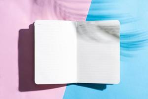 Libro abierto en blanco sobre fondo azul y rosa, concepto de verano foto