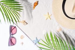 fondo de verano con concha, gafas de sol y sombrero en la arena foto