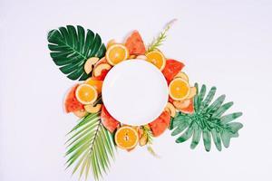 el plato vacío se coloca sobre trozos de fruta tropical foto