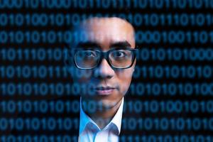 Portrait of Asian businessman with lines of code on his face. Concept of human being digitized in the future photo