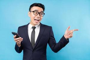 Buisnessman asiático vistiendo traje sosteniendo smartphone sobre fondo azul. foto