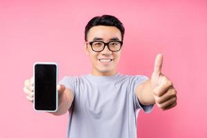 Retrato de hombre asiático con smartphone sobre fondo rosa foto
