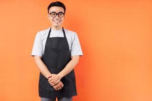 Portrait of Asian male waiter posing on orange background photo