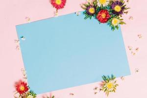 el papel azul se coloca sobre un fondo rosa con flores alrededor de hoa foto