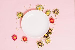 el plato blanco redondo se coloca sobre un fondo rosa con flores alrededor foto