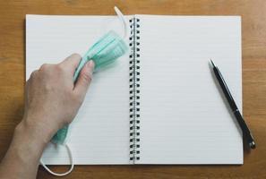Mano usando la fase de escritura de lápiz en el libro diario con mascarilla quirúrgica en la parte superior de la mesa de madera. covid-19, coronavirus y nuevo concepto de estilo de vida normal foto