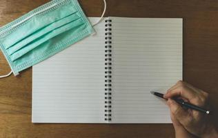 Writing in notebook at desk photo