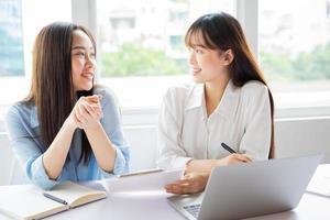 La empresaria asiática y sus colegas discutiendo trabajar juntos foto