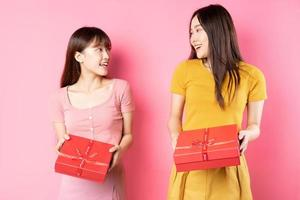 Retrato de dos hermosas jóvenes asiáticas sosteniendo una caja de regalo roja sobre un fondo de color rosa foto