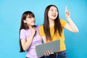 Dos hermosas jovencitas asiáticas usando un portátil sobre fondo azul. foto