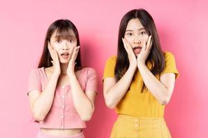 retrato, de, dos, hermoso, joven, niñas asiáticas, posar, en, fondo rosa foto