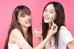 dos hermosas jovencitas asiáticas haciendo maquillaje el uno al otro foto