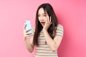 Joven mujer asiática con smartphone sobre fondo rosa foto