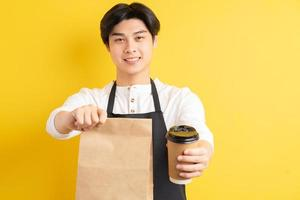 Portrait of male waiter holding paper cup in hand on yellow background photo