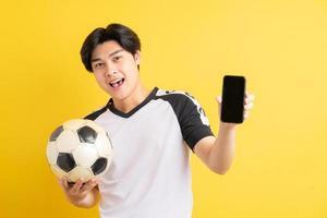 el hombre asiático está sosteniendo una pelota y apuntando al teléfono con una pantalla en blanco foto